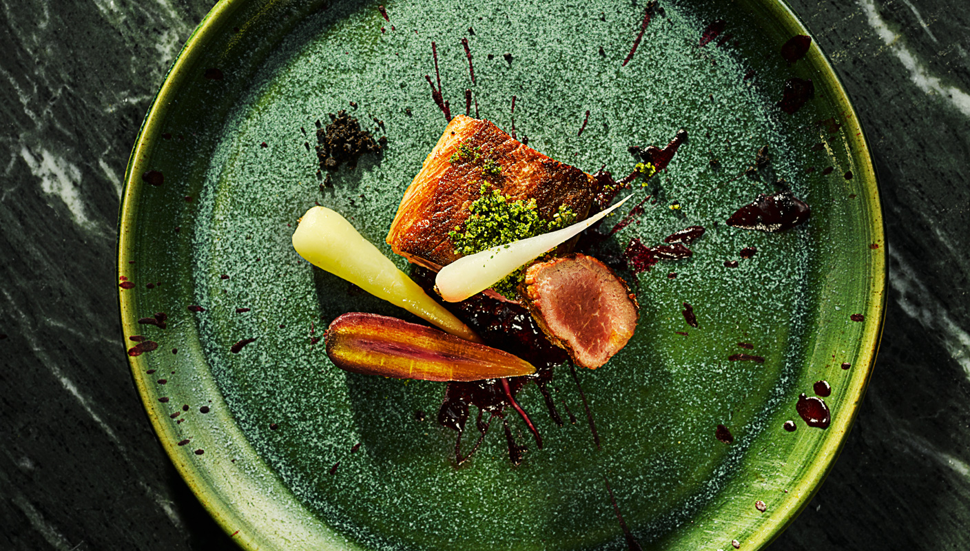 chef presented Roasted lamb with carrots on vibrant green textured plate by London food photographer Michael Michaels