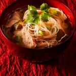 Thai Chicken Noodle Soup on red textured background