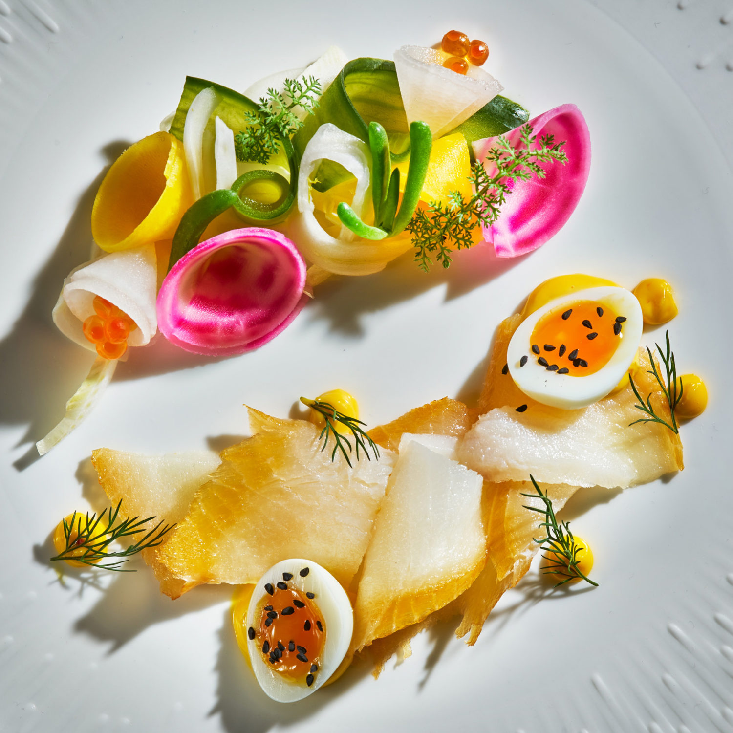 Smoked Halibut with quail egg, pickled beetroot, shaved fennel on white patterned plate.