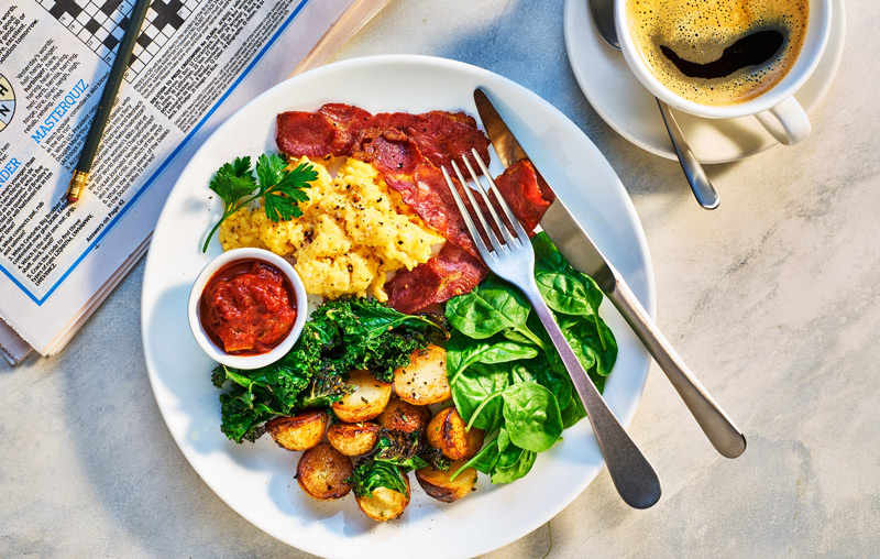 Photo of healthy cooked breakfast of bacon, scrambled eggs, kale and saute potatoes by London food photographer Michael Michaels