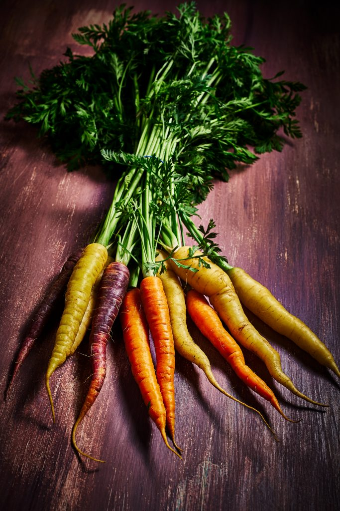 food photography of a bunch of multi coloured carrots, shots on a distressed mauve painted surface.