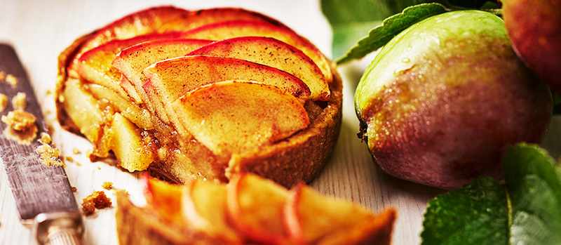 Apple tartlet with apple on branch and small slice cut away