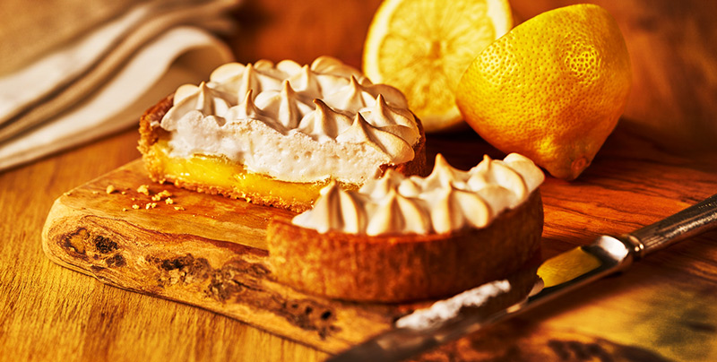 Lemon Meringue-tart on wooden board with 2 half lemons
