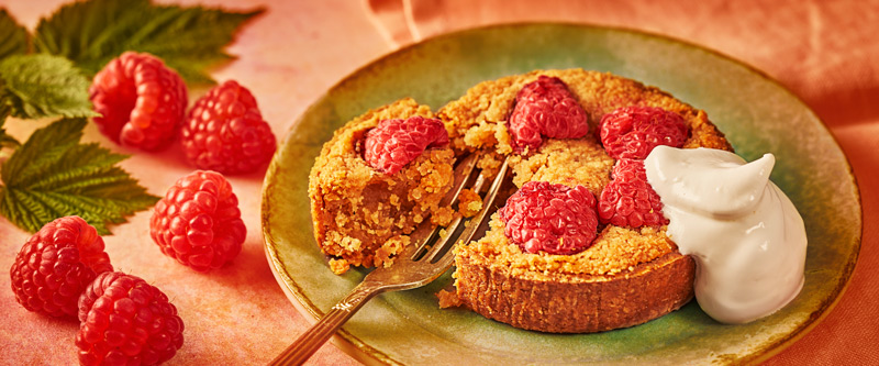 Raspberry Franzipan Tart by on pink cloth and napkin with raspberries on background