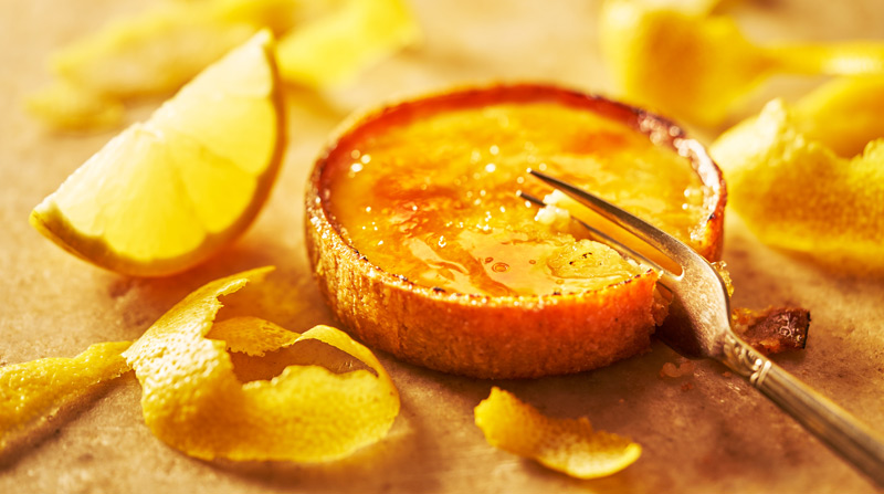 Tarte-au-citron surrounded in lemon zest and wedges with fork cutting into tart